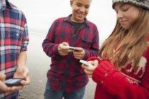 Подростки смотрят на смартфоны на берегу озера . — стоковое фото
