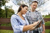 Man and woman using digital tablet at organic farm. — Stock Photo