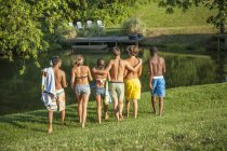 Grupo médio de meninos e meninas adolescentes caminhando através do campo verde para o lago . — Fotografia de Stock