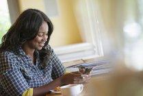 Mitte erwachsene Frau checkt Smartphone am Tisch im Café. — Stockfoto