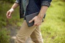 Куповані зору людини, несучи цифровий планшет на відкритому повітрі. — стокове фото