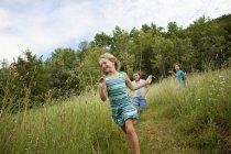 Tre ragazze ridendo e correndo attraverso l'erba verde . — Foto stock
