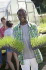 Young man holding trays of green seedlings with couple talking by greenhouse. — Stock Photo