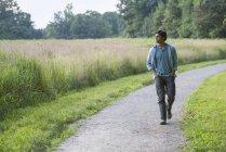 Jovem homem andando caminho rural com as mãos nos bolsos. — Fotografia de Stock