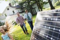 Mitte Erwachsenen Mannes mit Sohn und Tochter, die zu Fuß durch Solar-Panel im Bauerngarten — Stockfoto