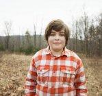 Adolescent dans la position de la chemise à carreaux rouges dans la forêt automnale. — Photo de stock