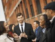 Бізнесмен, стоячи на вулиці з мобільного телефону і групи людей в Нью-Йорк, США. — стокове фото