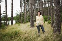 Mulher em pé na grama alta na costa do lago país — Fotografia de Stock