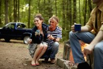 Young friends sitting around campfire at dusk with truck in woods. — Stock Photo