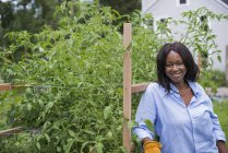 Woman leaning on fence and smiling in vegetable garden. — Stock Photo