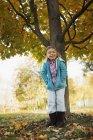 Niña de edad elemental de pie bajo el árbol otoñal en la granja . - foto de stock