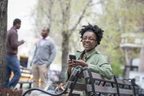 Woman on bench checking phone with two men in background. — Stock Photo