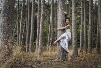 Mulher abraçando árvore enquanto dança e olhando na câmera na floresta . — Fotografia de Stock