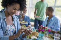 Женщина с помощью смартфона и улыбаясь во время ужина с друзьями в интерьере загородного дома . — стоковое фото