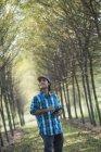 Homem em pé na avenida das árvores e segurando tablet digital . — Fotografia de Stock