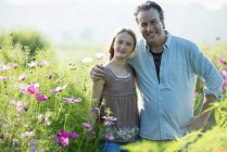 Mature man with daughter posing in green field of flowers. — Stock Photo