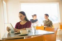 Frau in Coffee-Shop mit Tablet-PC mit Menschen reden im Hintergrund lesen — Stockfoto