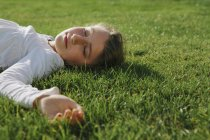 Elementary age girl resting on green grass with eyes closed — Stock Photo