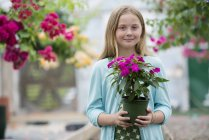 Pre-adolescent girl holding potted flowers at organic plant nursery and looking in camera. — Stock Photo