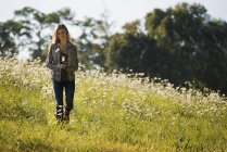 Young woman walking in wild flowery meadow. — Stock Photo