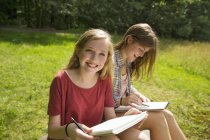 Two teenage girls sitting on grass with notebooks and pencils. — Stock Photo
