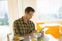 Молодой человек использует цифровые планшеты в кофейне . — стоковое фото