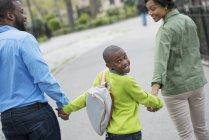 Хлопчик з рюкзака дивлячись через плече, під час прогулянки з батьками на вулиці — стокове фото