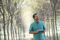 Man standing in avenue of trees and holding digital tablet. — Stock Photo