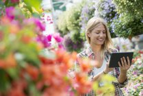 Young woman examining flowers with digital tablet in plant nursery. — Stock Photo