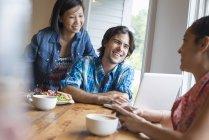Freunde teilen Laptop, unterhalten sich und nutzen Smartphone am Tisch im Café. — Stockfoto
