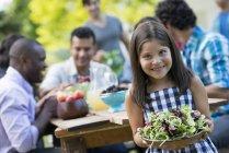 Grundschulkind Mädchen hält Schüssel Salat mit Erwachsenen an Tisch im Garten — Stockfoto