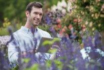 Средний взрослый мужчина с помощью цифровых таблеток в органических растительных питомниках . — стоковое фото
