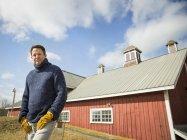 Uomo in posa di fronte a fienile in fattoria . — Foto stock