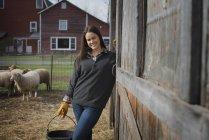 Jovem agricultora segurando balde de água na fazenda . — Fotografia de Stock