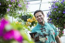 Young man holding digital tablet in flower greenhouse of plant nursery. — Stock Photo