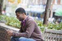 Jeune homme assis sur le banc et vérifier le téléphone en ville . — Photo de stock