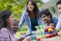 Friends sitting at outdoor table in garden with fruits and vegetables. — Stock Photo