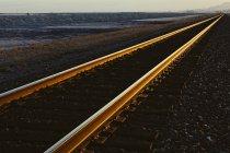 Binari ferroviari che si estendono attraverso pianeggiante paesaggio desertico dello Utah al tramonto, Stati Uniti . — Foto stock