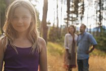 Elementary age girl with blonde hair standing in woodland with adults in background. — Stock Photo