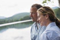 Casal maduro em pé na margem do lago e olhando para a vista . — Fotografia de Stock