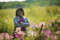Woman standing in meadow with arms folded at organic flower farm — Stock Photo