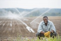 Young male farmer in working clothes on organic field with irrigating water sprinklers. — Stock Photo