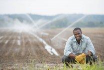 Jovem agricultor masculino na roupa de trabalho no campo orgânico com aspersores de água de irrigação. — Fotografia de Stock