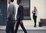Frau benutzt Smartphone mit zwei Männern, die auf Kopfsteinpflaster vorbeilaufen. — Stockfoto