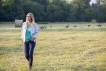 Woman walking across field with flock of geese outdoors. — Stock Photo