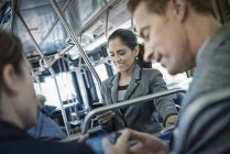 Men talking on bus with woman using smartphone in background. — Stock Photo