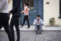 Man sitting on sidewalk and checking phone with passers-by on street. — Stock Photo