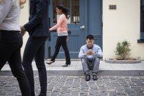 Homem sentado na calçada e verificando o telefone com os transeuntes na rua. — Fotografia de Stock