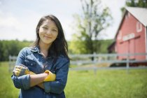 Young woman standing in front of traditional farm house in countryside. — Stock Photo