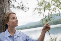 Mature woman holding twig on shore of lake in countryside. — Stock Photo